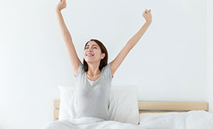 Sleep Wellness Link - Woman waking up and streching
