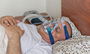 Weight Loss Link - Man with CPAP Mask Sleeping